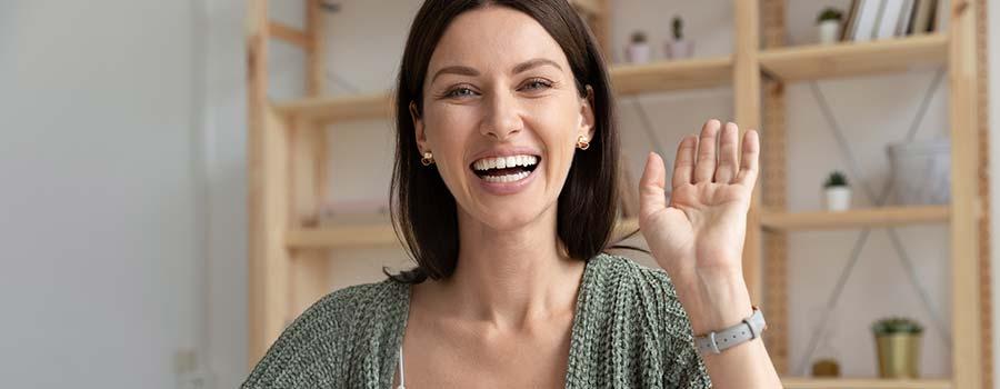 glückliche Frau winkt
