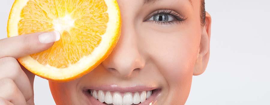 Frau hält sich eine Orangenscheibe vor das Auge
