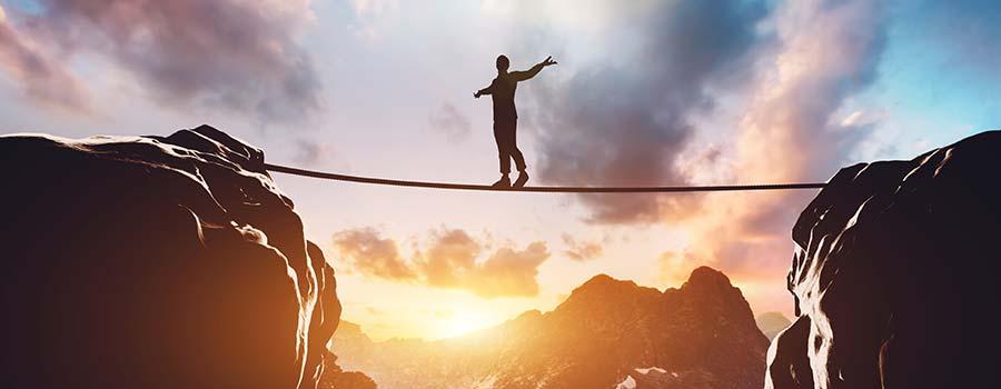 Mensch balanciert mutig auf einem Seil