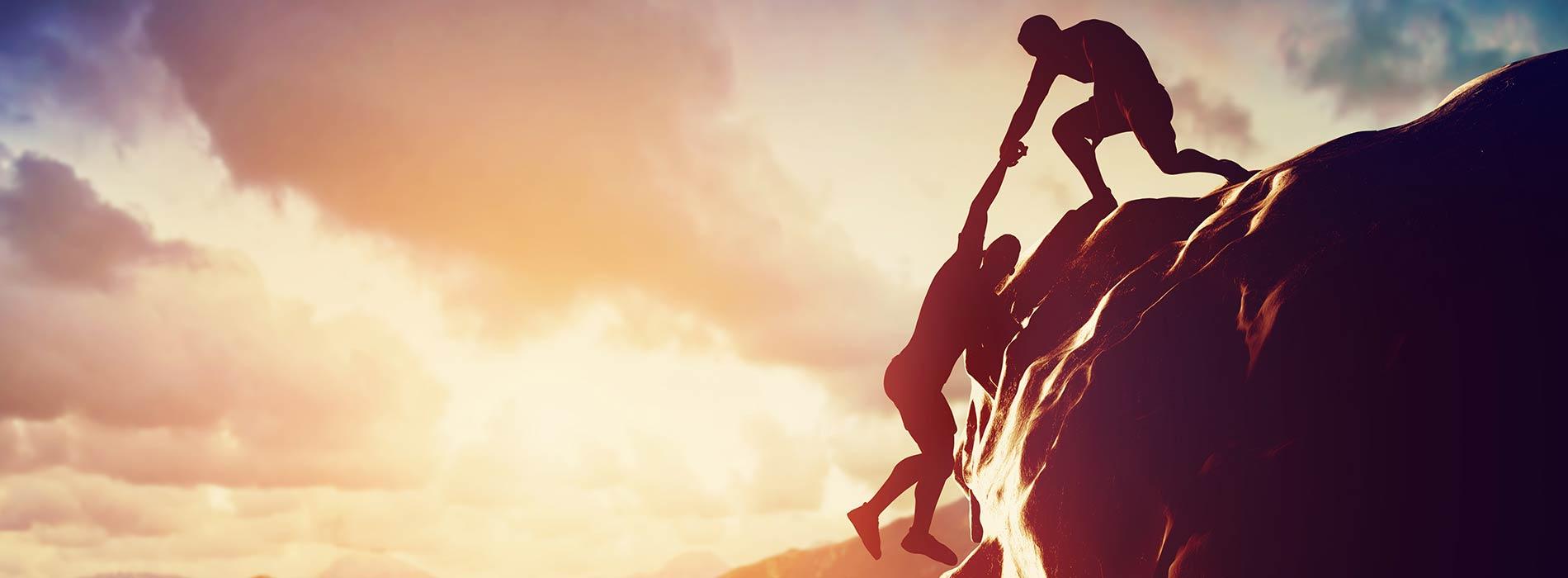 Mann hilft beim Berg steigen seinem Freund