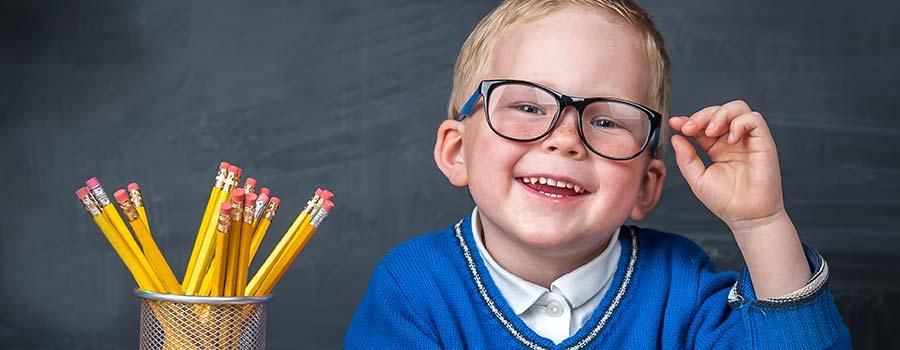 Junge greift sich lachend an die Brille
