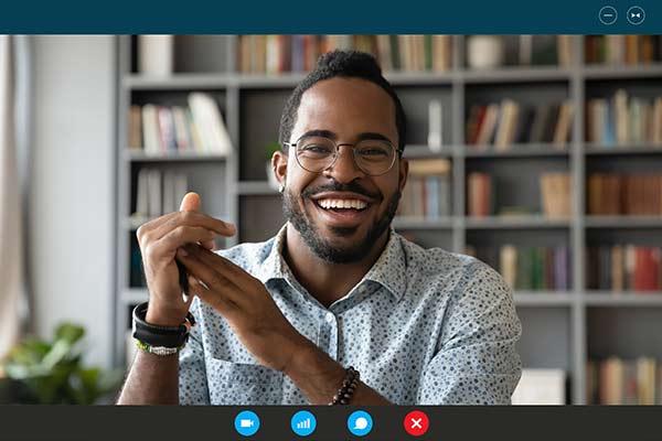 Mann lacht in die Webcam beim Online Coaching