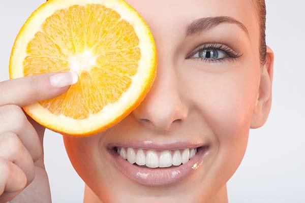angeschnittene Orange vor dem Gesicht einer Frau