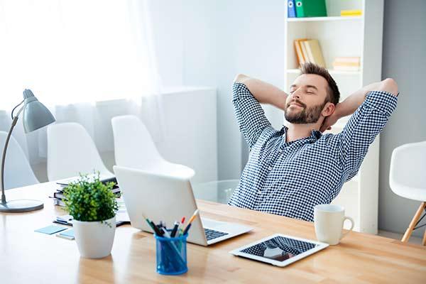 Mann am Schreibtisch hält inne und entspannt