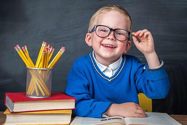 kleiner Junge am Schreibtisch stolz auf seine Brille