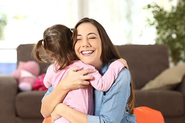 Kind wird liebevoll von ihrer Mutter umarmt