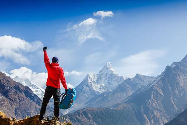 Mann steht in den Bergen und hebpt stolz seinen Arm in die Luft