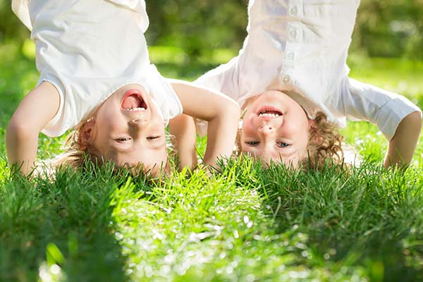 glückliche Kinder beim Kopfstand auf dem Rasen