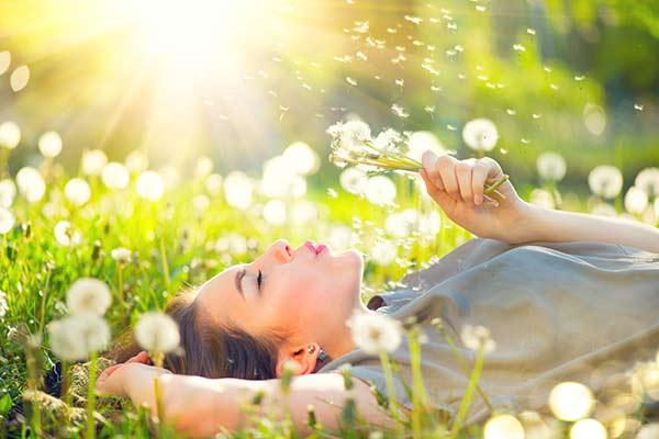 entspannte Frau liegt auf der Pusteblumen-Wiese