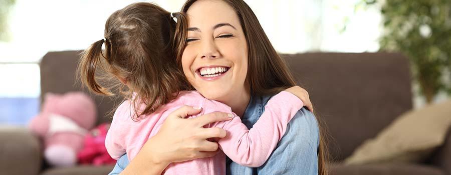 Mutter umarmt glücklich ihre Tochter