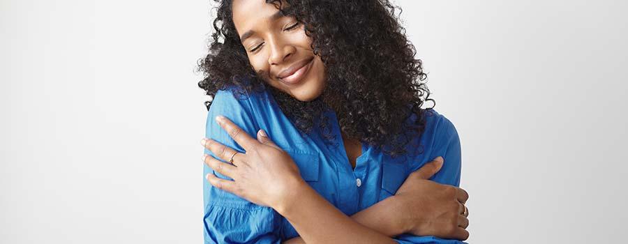 glückliche Frau umarmt sich selbst