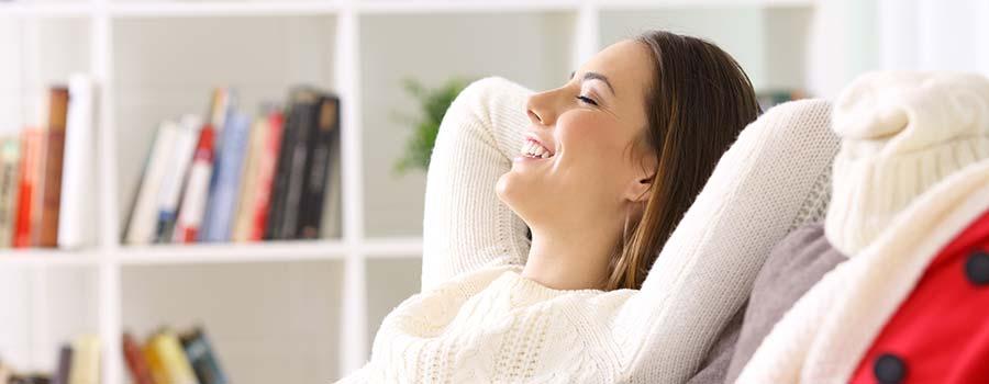 Frau entspannt zufrieden auf der Couch