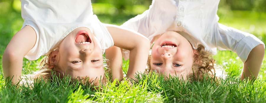 Kinder stehen Kopf auf der Wiese