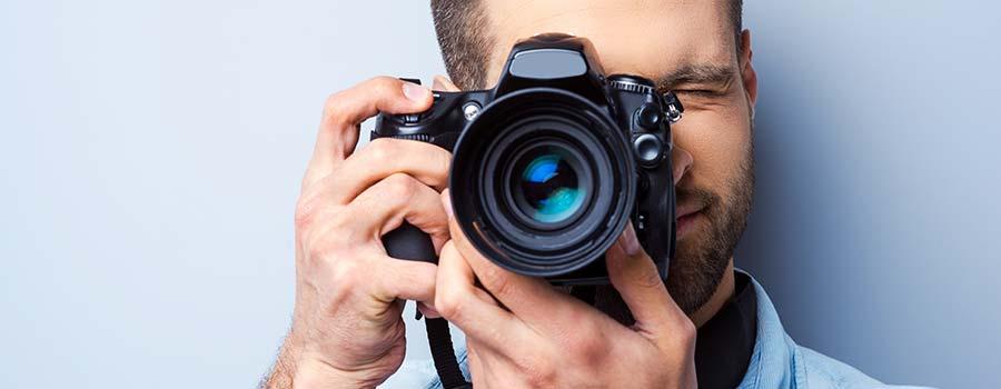 Mann hält seine Fotokamera in die Kamera