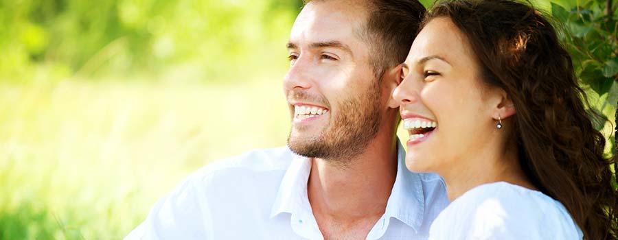 Mann und Frau sitzen glücklich auf einer Wiese