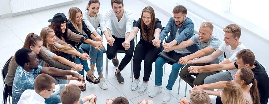 Fröhliche Teilnehmer im Stuhlkreis halten sich die Hände
